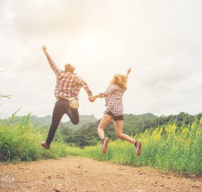 Young hipster couple in love outdoor jumping at yellow flower field with mountain sunset background. Jump up high enjoying freedom and enjoy.